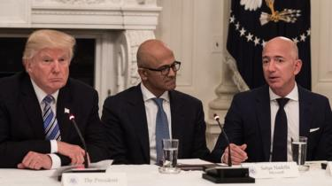 US President Donald Trump (L) and Microsoft CEO Satya Nadella (C) listen to Amazon CEO Jeff Bezos (R) during an American Technology Council roundtable at the White House in Washington, DC, on June 19, 2017.