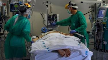 Tim medis merawat pasien yang sedang dalam posisi tengkurap.