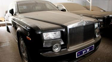Des véhicules de luxe empoissiérés, ici une Rolls-Royce, dans le parking du palais à Banjul.