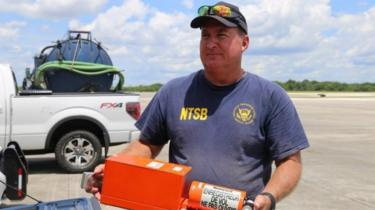A National Transportation Safety Board (NTSB) investigator is seen with flight data recorder