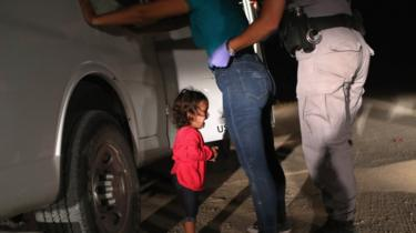 A two-year-old Honduran asylum seeker cries as her mother is searched and detained near the US-Mexico border on 12 June 2018 in McAllen, Texas.