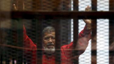 Deposed President Mohamed Mursi greets his lawyers and people from behind bars at a court wearing the red uniform of a prisoner sentenced to death, during his court appearance with Muslim Brotherhood members on the outskirts of Cairo, Egypt, June 21, 2015