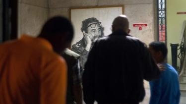Cubanos reúnem-se em frente de um retrato de Fidel Castro
