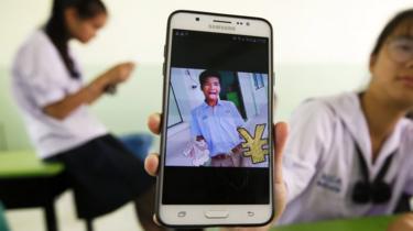 A Thai student shows an image of her classmate Panumas Sangdee,