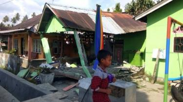 A boy walking in front of a collapsed house after a 6.1 magnitude earthquake that hit in Donggala, Central Sulawesi, Indonesia, 28 September 2018.