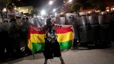 A woman stands in front of police