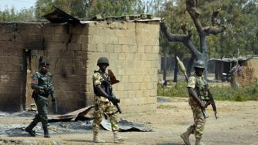 Soldiers and policemen walk past burnt house on 4 February 2016 during a visit to the village of Dalori village, Borno state, after Boko Haram attack