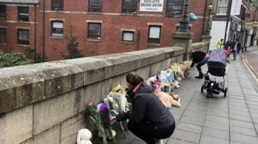 People leaving floral tributes