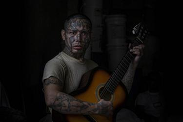 An inmate and former La 18 gang member plays the guitar at the Penal San Francisco Gótera, El Salvador. November 8, 2018.