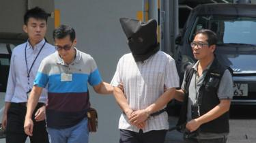 Khaw Kim-sun, wearing a black hood over his face, being escorted by police at Ma On Shan Police Station in Hong Kong