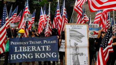 """Us flags abound in this photo of protesters standing by a sign which reads """"President Trump, Please liberate Hong Kong!"""""""