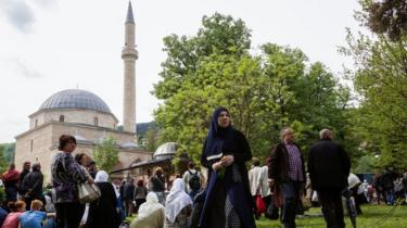 A woman stands in front of a crowd in front of the mosque