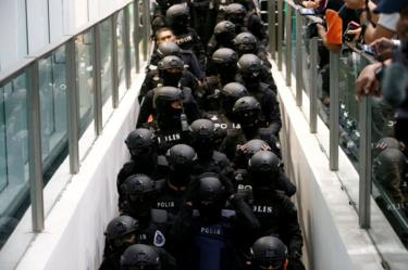 Armed policemen take the escalator as they escort Indonesian Siti Aisyah and Vietnamese Doan Thi Huong, who are on trial for the killing of Kim Jong Nam, the estranged half-brother of North Korea