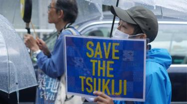 A protester stands in the rain with a sign saying Save the Tsukiji