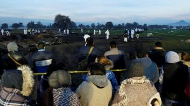Relatives gather at the scene as forensic workers carry out inspections