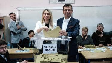Turkish main opposition party CHP's Istanbul mayoral candidate Ekrem Imamoglu and his wife pose as they cast their votes at a polling station in Istanbul