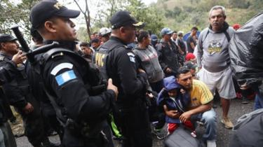 Honduran migrants wait as police block a road to a border checkpoint into Guatemala on 16 January, 2019 in Agua Caliente,