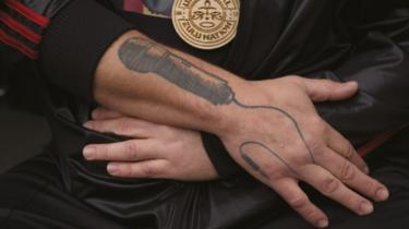 Close up showing tattoo of microphone on Steve's lower arm