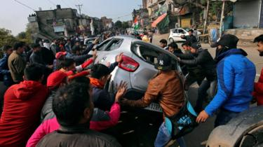 Demonstrators overturn a car during a protest against the attack on a bus that killed 44 Central Reserve Police Force (CRPF) personnel in south Kashmir on Thursday, in Jammu February 15, 2019.