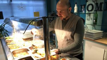 Ahmet Acikel serving food
