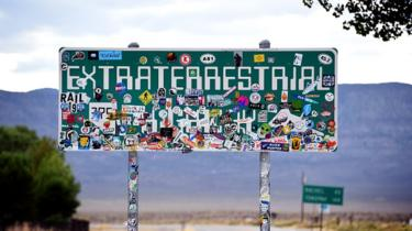 An Extraterrestrial Highway sign covered with stickers is seen along state route 375