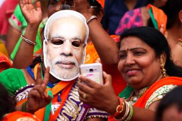 Indian supporters of the Bhartiya Janta Party (BJP), with one wearing a mask of Prime Minister Narendra Modi, take a selfie