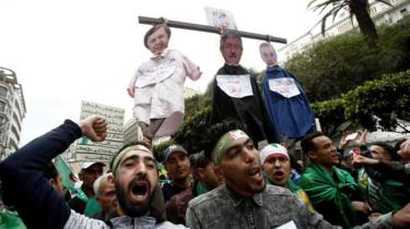 People gesture and carry a mock hangman with the faces of Algerian businessman Ali Haddad, former prime minister Ahmed Ouyahia, and Said Bouteflika, brother of former Algerian president Abdelaziz Bouteflika, during a protest to push for the removal of the current political structure, in Algiers, Algeria April 5, 2019.