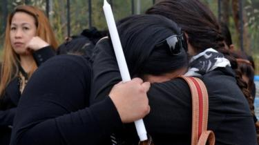 Two women hug, one clutching a candle, at the public vigil in memory of the serial killer's victims