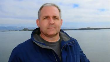 Paul Whelan poses in front of a body of water