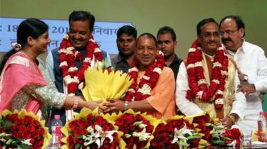 "Senior Leader of India""s Bharatiya Janata Party (BJP) M. Venkaiah Naidu (R) Uttar Pradesh BJP Leaders Prasad Maurya (2L) and Dinesh Sharma (2R) look on as Yogi Adityanath (C) is presented with a floral bouquet during a ceremony in Lucknow on March 18, 2017,"