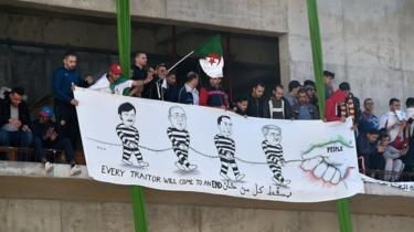 "People hold a banner calling the president, the general secretary of the General Union of Algerian Workers (UGTA), the chairman of Algeria's Forum des chefs dentreprises (FCE), and the former prime minister ""traitors""."