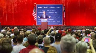 Trump discursa no palanque, observado por dezenas de pessoas