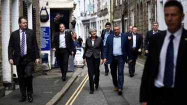 Britain's Prime Minister Theresa May (C) is flanked by security guards as she walks in Mevagissey, south-west England, during the 2017 election campaign