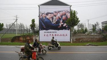 A poster of President Xi Jinping visiting people living in poverty