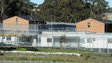 An external view of Villawood Immigration Detention Centre, showing two brick buildings enclosed by high fences