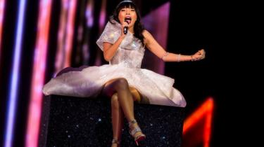 Singer Dami Im sits on a glittery box in a sparkly white dress with her legs crossed