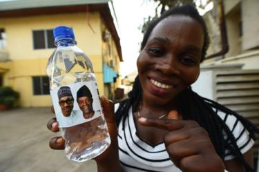 A woman smiles as she holds a bottle of water branded with the faces of President Muhammadu Buhari and the vice-president in Abuja, Nigeria - Wednesday 20 February 2019