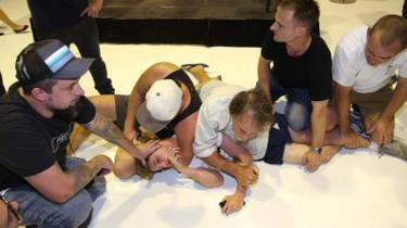 Will Connolly pinned to the ground by five men following his egg-cracking protest