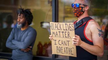 """Un hombre blanco sosteniendo un cartel que dice """"Las vidas negras importan. No puedo respirar""""."""