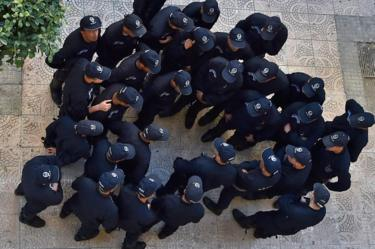 Algerian anti-riot police are seen from above, huddling in a group.