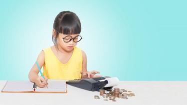 فتاة أمامها أموال وورقة وقلم وآلة حاسبة