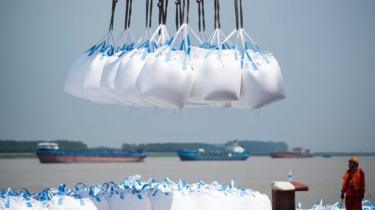 This photo taken on August 7, 2018 shows workers unloading bags of chemicals at a port in Zhangjiagang in China's eastern Jiangsu province