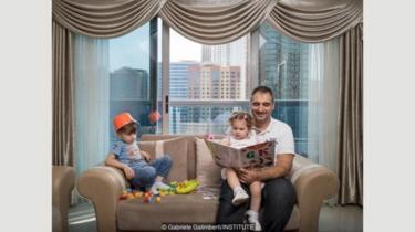Fouad Kuyali membaca untuk anaknya, Mazen dan Julie, di rumah mereka di Dubai, setelah mereka pindah dari Aleppo, Suriah.