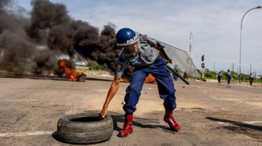 Riot police removing a burnt tyre