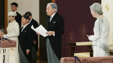 Japan's Emperor Akihito, flanked by Empress Michiko, delivers his final address as emperor