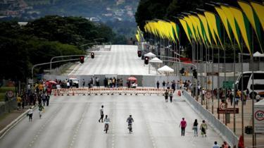 Vista ampla de pista em Brasília com pontos de bloqueio, alguns pedestres e bandeiras em verde e amarelo