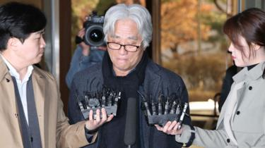 Theatre director Lee Yoon-taek is surrounded by reporters as he appeared for police questioning on 17 March