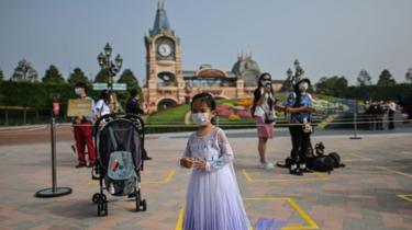 A girl wearing a face mask waits to enter the Disneyland amusement park in Shanghai on May 11, 2020