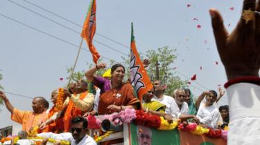 Uttar Pradesh Chief Minister Yogi Adityanath and Union Minister Smriti Irani wave at the crowd during a road show before filing her nomination papers on April 11, 2019 in Amethi, India.