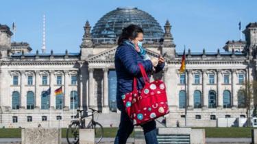 امرأة تمر بالقرب من الرايخستاغ في برلين مرتدية قناعاً للوجه